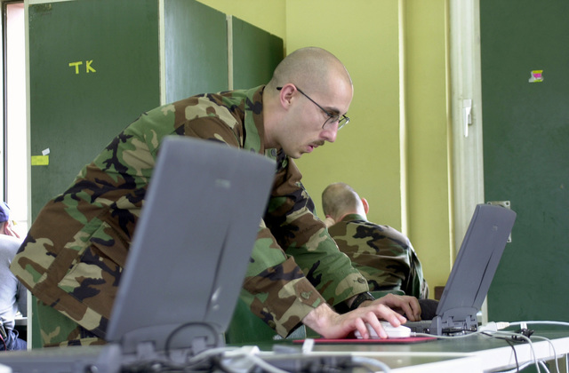 US Army (USA) Sergeant First Class (SFC) Earl Allen (foreground), a systems administrator with the 5th Signal Corps, prepares a computer for use during Exercise COMBINED ENDEAVOR 2002, at Lager Aulenbach, Germany