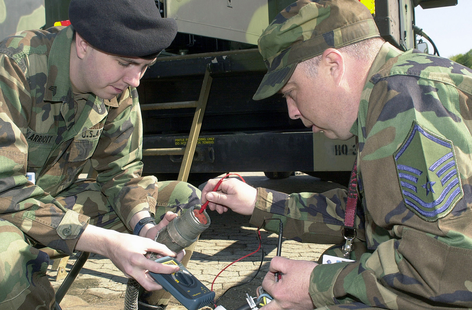 US Army (USA) Sergeant (SGT) Nick Marriott (left), Information Analyst, 7th Signal Brigade, and US Air Force (USAF) MASTER Sergeant (MSGT) Billy Hackleman, 86th Communications Squadron (CS), set up a power supply during Exercise COMBINED ENDEAVOR 2002, at Lager Aulenbach, Germany