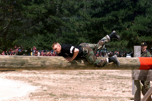 """US Air Force (USAF) AIRMAN First Class (A1C) Terrick Turner, a Security Police (SP) assigned to the 91st Space Wing (SW), Minot Air Force Base (AFB), North Dakota (ND), throws his legs over the """"Belly Buster"""" during the Security Forces Obstacle Course competition conducted at Vandenberg Air Force Base (AFB) California (CA), during Exercise GUARDIAN CHALLENGE 2002. Guardian Challenge, a four-day space and missile competition, is hosted annually at Vandenberg AFB, CA to test the wartime readiness of Air Force Space Command (AFSPC) professionals"""