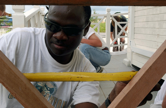 US Marine Corps (USMC) member, Hypolite, with landing force Cooperation Afloat Readiness and Training (CARAT), constructs a new fence for the facility for the mentally and physically handicapped
