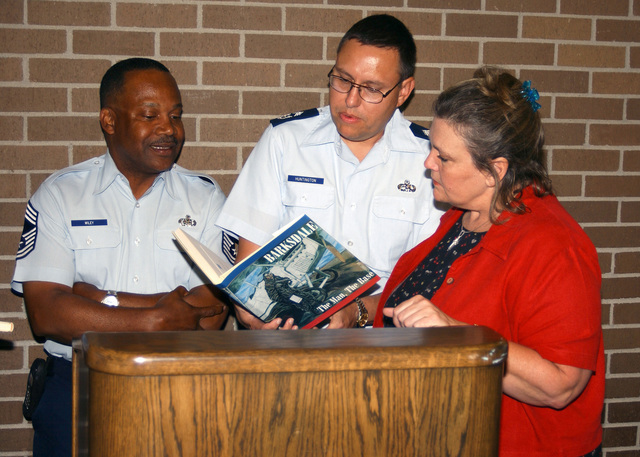 US Air Force (USAF) CHIEF MASTER Sergeant (CMSGT) Sylvester Wiley (left) and USAF CMSGT Ralph Huntington (center), both assigned to Headquarters, Eighth Air Force, Barksdale Air Force Base, (AFB) Louisiana (LA), present a book on the history of Barksdale AFB to Sue Rice, Administrator, Arkansas Schools District, Arkansas City, Arkansas (AR)