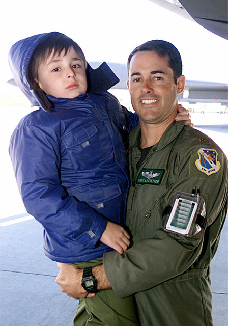 US Air Force (USAF) Major (MAJ) Vincent Lostetter, a B-1B Lancer aircraft Pilot assigned at Ellsworth Air Force Base (AFB), South Dakota (SD), poses for a photograph holding Tadd Sharp, a child selected during the Pilot For A Day Program at Ellsworth AFB. The Program takes terminally ill or disadvantaged children from the local community and shows them what it's like to be a USAF pilot for a day