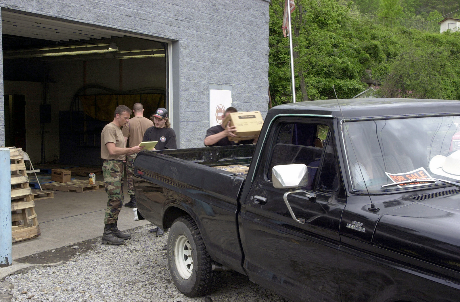 US Air Force (USAF) Technical Sergeant (TSGT) James Marcum, and personnel assigned to the Fire Department, 130th Airlift Wing (AW), West Virginia (WV) Air National Guard (ANG) distribute, water, cleaning supplies and household staples to a resident of Kimball, WV, after floods devastated the Southern part of the State