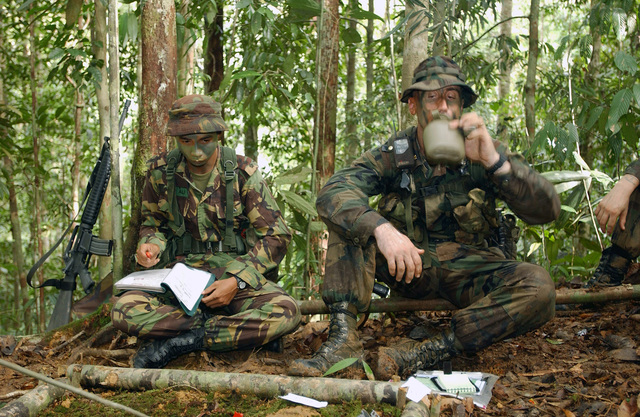 Deep in the jungle, US Marine Corps (USMC) Major (MAJ) William Clark, with the ground combat element, landing force Cooperation Afloat Readiness and Training (CARAT), enjoys a drink with a member of the Royal Brunei Army