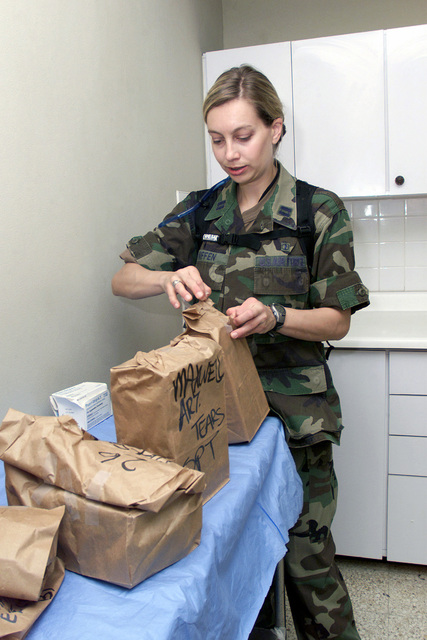 US Air Force (USAF) Captain (CPT) Chris Kniffen, Optometrist, 377th Aerospace Medicine Squadron (AMDS), sorts through and organizes medical supplies for delivery to local residents at the Mayfield Park Medical Center, while deployed to Kingston, Jamaica as part of Exercise NEW HORIZONS 2002