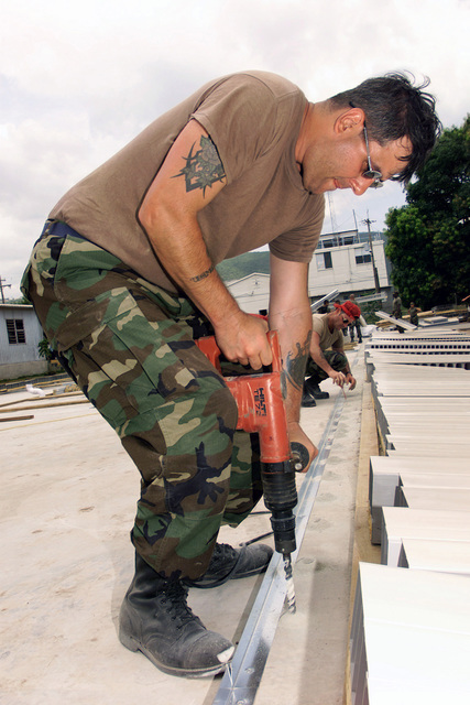 US Air Force (USAF) SENIOR AIRMAN (SRA) Joe DeMora, Utilities Technician, 201st Red Horse Flight (RHF), drills out the rebar mounts for wall reinforcement during construction of the new barracks for the Jamaican Defense Force at Camp Dingo, Kingston, Jamaica, during a Joint Task Force (JTF) humanitarian mission conducted during Exercise NEW HORIZONS 2002