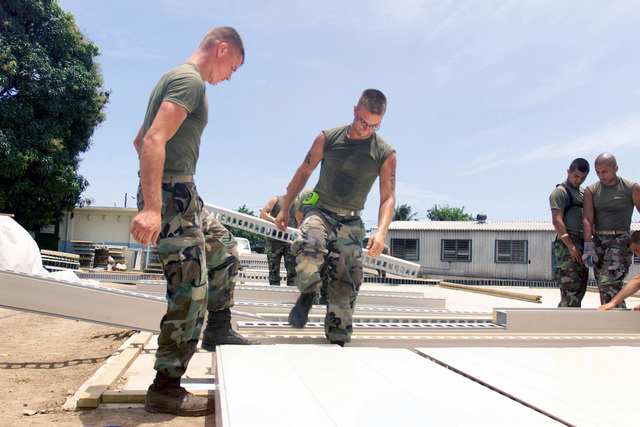 US Marine Corps (USMC) personnel assigned to Marine Wing Support Squadron 272 (MWSS-272) assemble wall joists during the construction of the new barracks for the Jamaican Defense Force at Camp Dingo, Kingston, Jamaica, during a Joint Task Force (JTF) humanitarian mission conducted during Exercise NEW HORIZONS 2002
