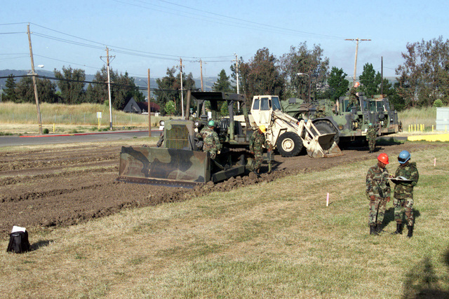 Captain (CPT) Darren M. Boarnet and First Sergeant (1SG) Luis Barraza (both to the right) from the 285th Combat Support Engineer Company, Baton Rouge, Louisiana, perform annual training with scrapers at Parks Reserve Forces Training Area. The 285th starts with a D7G Medium Bulldozer as they construct a parking area at Construction Project Site #2. In the background are a Case W24C AT-10K with a multi-purpose 4 in 1 bucket with teeth, and a couple of Caterpillar 621b scrapers