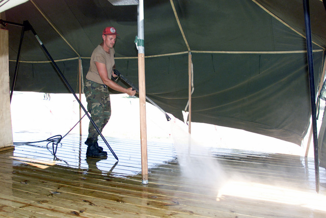 US Air Force (USAF) STAFF Sergeant (SSGT) Alan Finger, Utilities Technician, 200th Red Horse Flight (RHF), uses a high-pressure washer to sanitize the shower facilities at Camp Dingo in Kingston, Jamaica, during a Joint Task Force (JTF) humanitarian mission conducted during Exercise NEW HORIZONS 2002