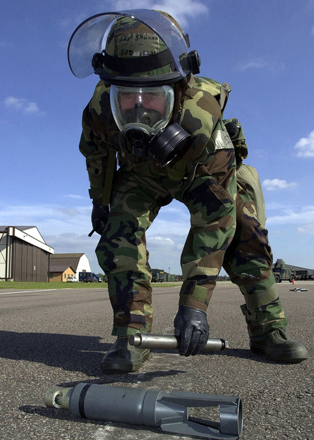 US Air Force (USAF) Technical Sergeant (TSGT) Jeffrey Shuman, 48th Civil Engineering Squadron (CES), Explosive Ordnance Disposal (EOD), wears Mission-Oriented Protective Posture response level 4 (MOPP-4) gear as he places a detonator next to an unexploded ordnance during the 48th FW Tactical Evaluation (TACEVAL) Exercise held at Royal Air Force (RAF) Feltwell, United Kingdom (UK)