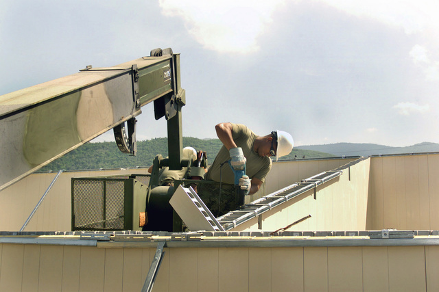 US Marine Corps (USMC) Sergeant (SGT) Dereck Lancaster, Electrician, Marine Wing Support Squadron 272 (MWSS-272), attaches a wall brace during the construction of the new medical clinic at Camp Dingo in Kingston, Jamaica, during a Joint Task Force (JTF) humanitarian mission conducted during Exercise NEW HORIZONS 2002