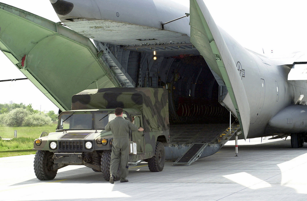 US Air Force (USAF) Technical Sergeant (TSGT) Lee Dockman, a C-141B Starlifter aircraft Loadmaster assigned to the 756th Airlift Squadron (AS), helps to upload a M1035 High-Mobility Multipurpose Wheeled Vehicle onto his aircraft at Kecskemet Air Base (AB), Hungary, during Exercise HUNGARIAN RESPONSE 2002