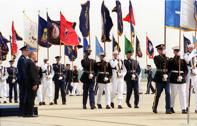 Chairman of the Joint Chiefs of STAFF, US Air Force (USAF) General (GEN) Richard B. Myers (left), and US Secretary of Defense (SECDEF), The Honorable Donald H. Rumsfeld, look on as Multi-Service Color Guards passes in review, during a Joint Service Open House Ceremony held at Andrews Air Forces Base (AFB), Maryland (MD)