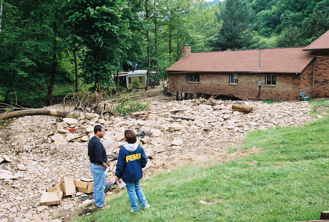 [Severe Storms, Flooding, and Landslides] Garland, WV, May 20, 2002 -- Mildred Avecedo talks with Wilbur Bishop, Jr. about his experiences on the afternoon of May 2, 2002 when a flash flood hit his south West Virginian home and nearly swept his wife away while she was in her tanning bed.  Bob McMillan/ FEMA Photo
