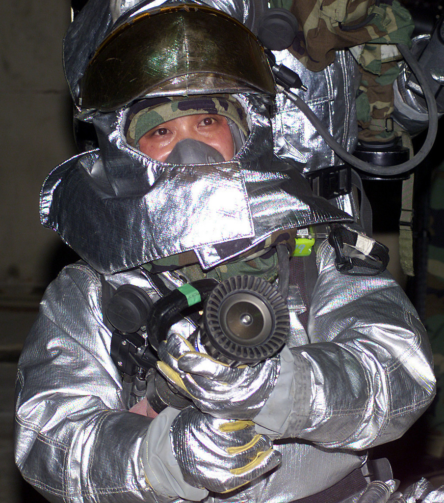 US Air Force (USAF) personnel assigned to the 51st Civil Engineer Squadron (CES) Fire Department, wear full proximity suites as they conduct pilot extraction dills during Exercise BEVERLY BULLDOG 02-02, at Osan Air Base (AB) Korea