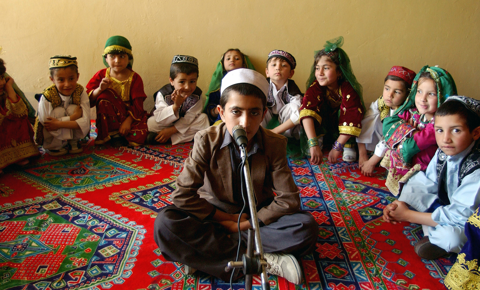 A young Afghani boy leads a song performed by students at the Asheiy School in Kabul, Afghanistan, during their International Children's Day Celebration. The songs were primarily about freedom from the Taliban and the promise of a better future