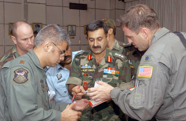 US Air Force (USAF) Major (MAJ) Manny Candelaria (left); India Army Colonel (COL) Paramjit Singh (center); Commander 4th Parachute Regiment, and USAF Lieutenant Colonel (LTC) Gregory Buterbaugh discusses a personnel air delivery mission while conducting combined exchange training with the Indian Armed Forces, at Air Force Station Agra, India. LTC Buterbaugh and MAJ Candelaria are both assigned to the 1ST Special Operations Squadron (SOS), 353rd Special Operations Group (SOG)