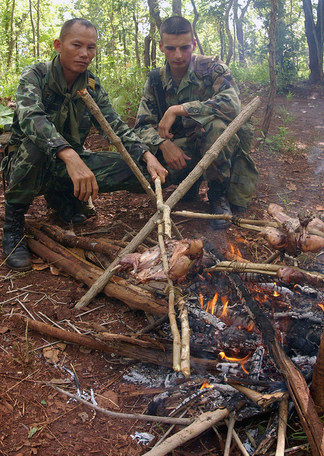 An unidentified Royal Thai Marine (left) and US Army (USA) Specialists Fourth Class (SPC4) Robert Visnick, an Infantryman assigned to 127th Bravo Company, cooks chicken over an open fire during jungle survival training held in Thailand, during Exercise COBRA GOLD 2002