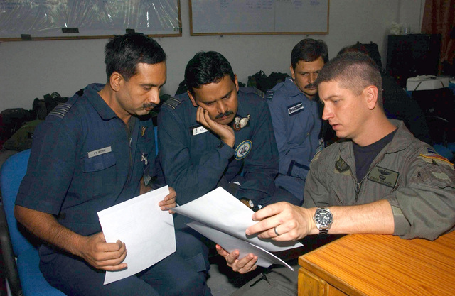 US Air Force (USAF) Captain (CPT) David Hanson (right), a Pilot assigned to the 1ST Special Operations Squadron (SOS), 353rd Special Operations Group (SOG), discusses mission procedures with Indian Air Force (IAF) Wing Commander, Partha Sarathi Bose (left); IAF Squadron Leaders Nand Kumar Nair (center) and IAF Sangeet Bhatnagan, in preparation from a airdrop training mission at Air Force Station Agra, India. Members of the 353rd SOG are deployed here for three weeks of joint combined exchange training with the Indian Armed Forces
