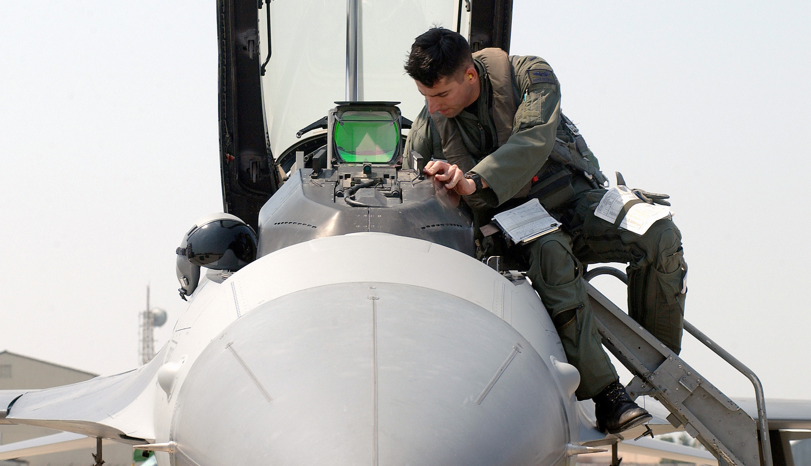 "US Air Force (USAF) First Lieutenant (1LT) Michael Driscoll, F-16C ""Fighting Falcon"" aircraft Pilot assigned to the 35th Fighter Squadron (FS), inspect the cockpit of his aircraft before a mission, on the flight line at Kunsan Air Base (AB), Republic of Korea (ROK)"