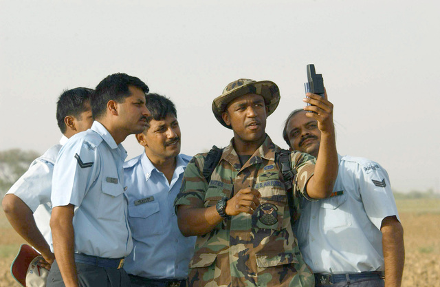 US Air Force (USAF) STAFF Sergeant (SSGT) Tony Yates (center), 353rd Operations Support Squadron, demonstrates a handheld Global Positioning System (GPS) on a drop zone near Agra airfield to members of the Indian Air Force (IAF). Members of the 353rd Special Operations Group are deployed here for three weeks of joint combined exchange training with the Indian Armed Forces