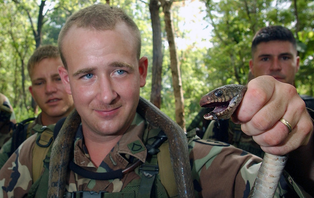 US Army (USA) Private First Class (PFC) Mark Ramsey, Infantryman, assigned to 127th Headquarter and Headquarters Company (HHC), holds up a cobra snake he caught during jungle survival training held in Thailand, during Exercise COBRA GOLD 2002