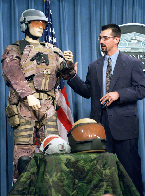 Mr. Dutch DeGay, Project Engineer for the Objective Force Warrior Program, conducts a Pentagon press briefing on the Armys prototype combat orm. The prototypes helmet incorporates infrared thermal, day/night video cameras, chemical-biological sensors, a global positioning system, broadcast heads-up display and ballistic protection. The torso garment incorporates body armor and has physiological status monitors that allows the individual soldier, as well as the medics on the battlefield, to know exactly what the individual soldiers physical condition is at any given time. The orm is suitable for all climate conditions, having the capability of being heated or cooled. The combat...