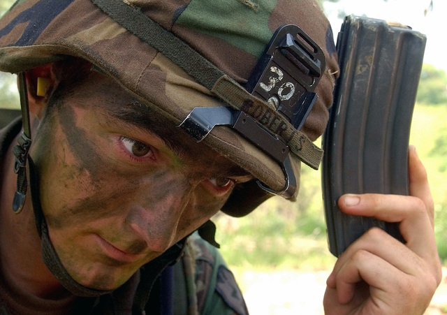 US Army (USA) Private (PVT) Zach Roberts, Infantryman, 1ST Battalion, 27th Infantry Regiment, taps his magazine on his helmet to prevent the cartridges from jamming prior to participating in a blank fire training exercise held in Thailand, during Exercise COBRA GOLD 2002