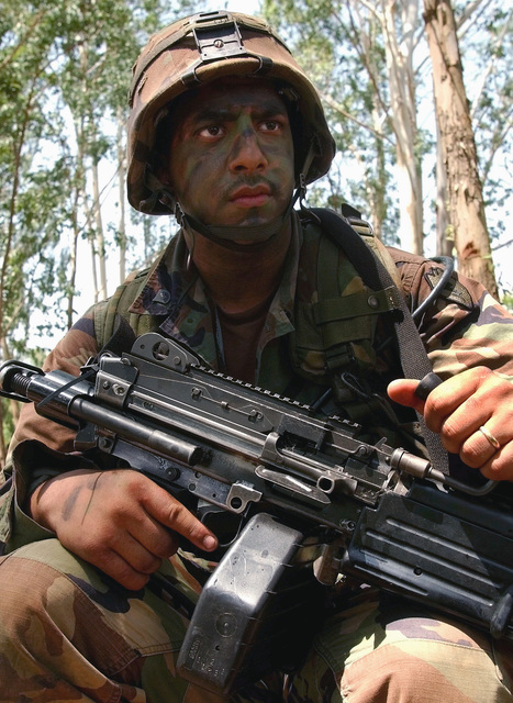 US Army (USA) Specialists Fourth Class (SPC4) Steve Colon, Infantryman, 1ST Battalion, 27th Infantry Regiment, carries his 5.56mm M249 Squad Automatic Weapon (SAW) as he awaits troop movement while conducting training exercises held in Thailand, during Exercise COBRA GOLD 2002