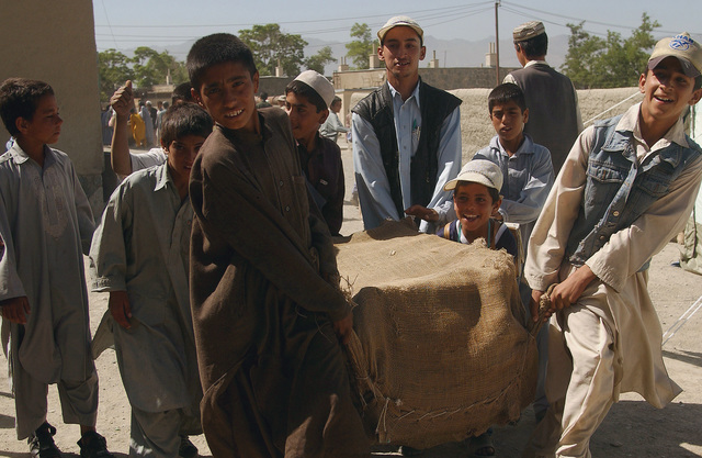 """Afghani Students at the Technical Academy Elementary School located near Kabul, Afghanistan, carry a bundle containing donated """"School-in-a-box"""" sets containing pens, pencils, notebooks and textbooks, during Operation ENDURING FREEDOM"""