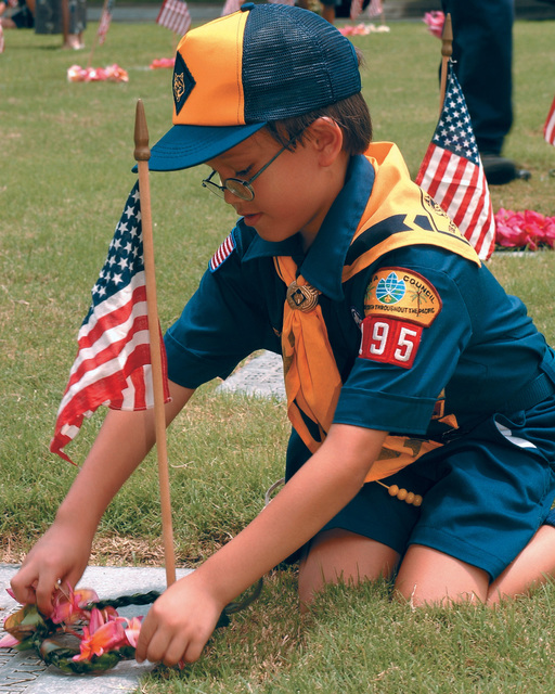 A Cub Scout from troop 195 of Oahu, Hawaii (HI) places a small lei and an American Flag onto a grave marker at the National Memorial Cemetery of the Pacific, during a Memorial Day Ceremony