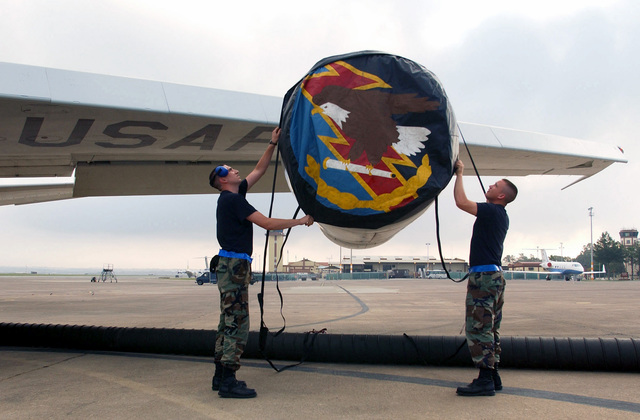 US Air Force (USAF) AIRMAN First Class (A1C) John Gill (left) and USAF A1C David Heaps, both assigned to the 552nd Aircraft Generation Squadron (AGS) place an engine cover over a jet aircraft engine, while deployed at Incirlik Air Base (AB), Turkey