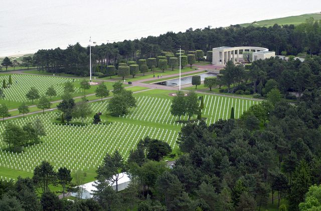 An aerial view showing the Normandy American Cemetery located in Normandy, France, with a portion of the coastline designated OMAHA BEACH during World War II (WW II). visible in the background