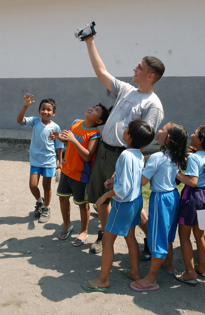 US Marine Corps (USMC) Lance Corporal (LCPL) Darrel Cramer, with the combat service support element, Landing Force Cooperation Afloat Readiness And Training (CARAT), plays with a group of children at a local Indonesian school, during the bilateral exercise