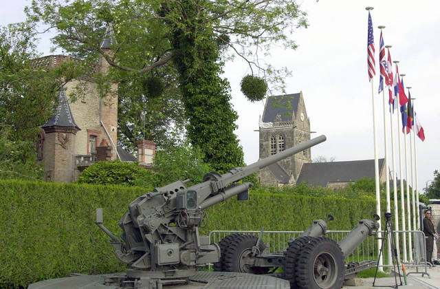 A US Army (USA) World War Two (WWII) M1A1 90mm antiaircraft gun sits in the middle of the town square, near the church of Sainte-Mere-Eglise, located in Eglise, France. During WWII the Church was the site where a USA Paratrooper, John Steel, found himself suspended in his harness and was used as a target by the enemy