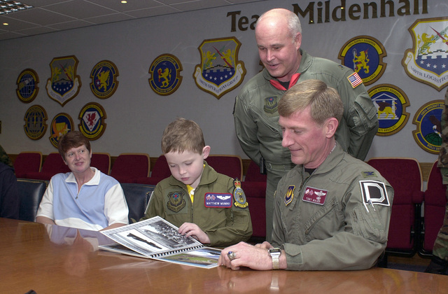 US Air Force (USAF) Colonel (COL) Jeffrey W. Walls (standing), Commander, 352nd Special Operations Group (SOG) and USAF COL Anthony Mauer (seated right), Commander, 100th Operations Group (OG), present Matthew Munro, a child selected for the Pilot for a Day Program at Royal Air Force (RAF) Mildenhall, United Kingdom (UK) at Wing photo book, as Mrs. Munro, the boys mother looks on. The Program takes terminally ill or disadvantaged children from the local community and shows them what its like to be an USAF pilot for a day