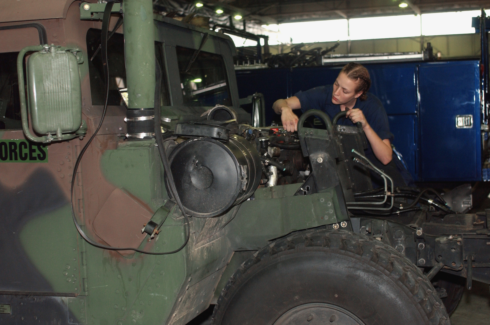 US Air Force (USAF) AIRMAN First Class (A1C) Megan Moon, Vehicle Maintenance Apprentice, 31st Transportation Squadron works performs maintenance on a M998 High-Mobility Multipurpose Wheeled Vehicle inside the maintenance shop at Aviano Air Base (AB), Italy