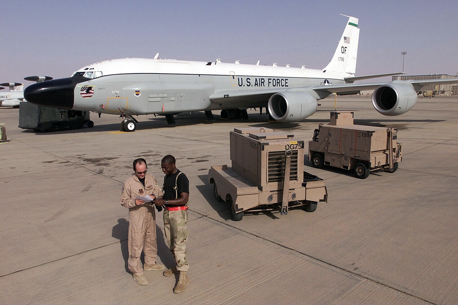 US Air Force (USAF) First Lieutenant (1LT) Dickie Waggoner (left), 763rd Expeditionary Reconnaissance Squadron, and USAF STAFF Sergeant (SSGT) Carlos Bennett Jr., Electrical and Environmental SPECIALIST, discuss the maintenance status of a USAF RJ-135 Embraer aircraft while deployed to Prince Sultan Air Base (AB), Saudi Arabia, in support of Operation SOUTHERN WATCH