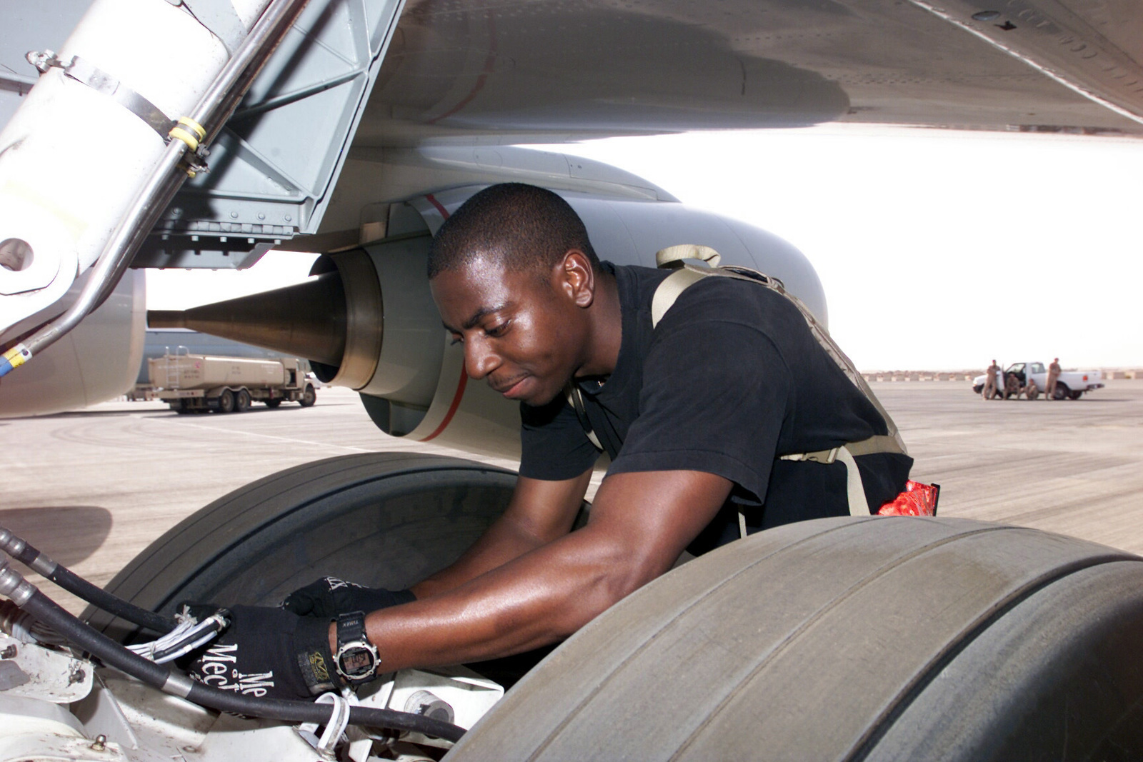 US Air Force (USAF) STAFF Sergeant (SSGT) Carlos Bennett Jr., Electrical and Environmental SPECIALIST, works on the landing gear electrical systems on a USAF RJ-135 Embraer aircraft while deployed to Prince Sultan Air Base (AB), Saudi Arabia, in support of Operation SOUTHERN WATCH