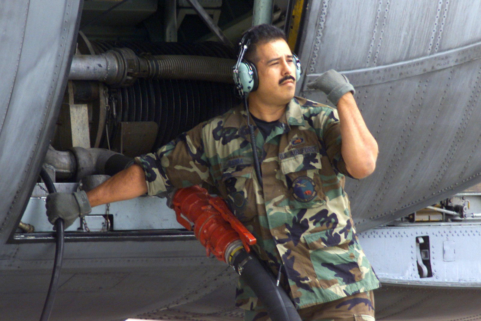 US Air Force (USAF) Technical Sergeant (TSGT) Victor Guerra, signals to cut off the flow of Phoschek, a chemical fire retardant, being pumped into a Module Airborne Fire Fighting System (MAFFS) unit aboard a US Air Force (USAF) C-130E Hercules aircraft at Channel Islands Air National Guard Station (ANGS), California (CA), as the California Department of Forestry prepares to fight numerous wildfires in California
