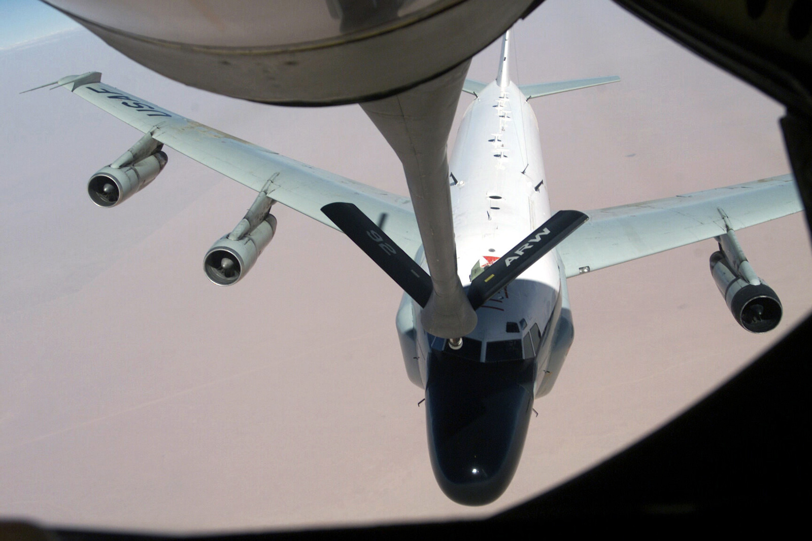 A US Air Force (USAF) RC-135V Rivet Joint aircraft assigned to the 763rd Expeditionary Reconnaissance Squadron (RES) approached the extended refueling arm of a USAF KC-135 Stratotanker aircraft assigned to the 92nd Air Refueling Wing (ARW) during aerial refueling conducted in support of Operation SOUTHERN WATCH