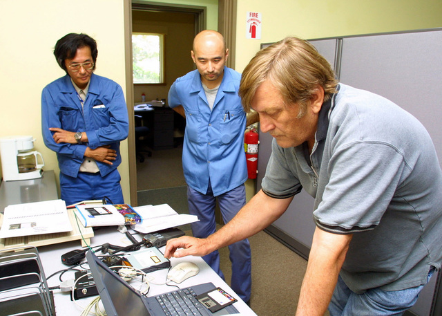 Mr. Alan E. Summer (right), Electronic/Mechanical Supervisor, 17th Area Support Group (ASG) Directorate for Support Operations (DSO) Maintenance Division, Sagami Depot, installs system software onto a PC as two other civilians look on