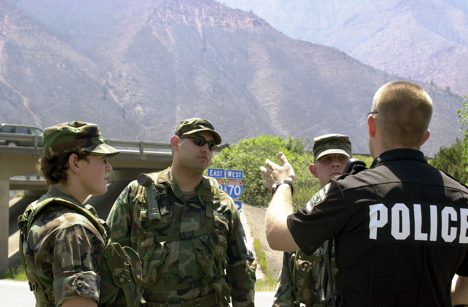 At an entrance to Interstate Highway 70 (I-70), a member of the Glenwood Springs Police Department brief members of the 220th Military Police (MP) Company, Colorado Army National Guard (COARNG) on the Coal Seam Fires. The 220th MP will set up security access control points along the perimeter including I-70. The Coal Seam Fire started sometime in the mid-1970s as an underground fire burned along a rich vein of coal. Occassionally the fire breaks through to the surface. At this time it had burned 7,300 acres, damaged an estimated 40 structures, and caused the evacuation of 2,000 residents