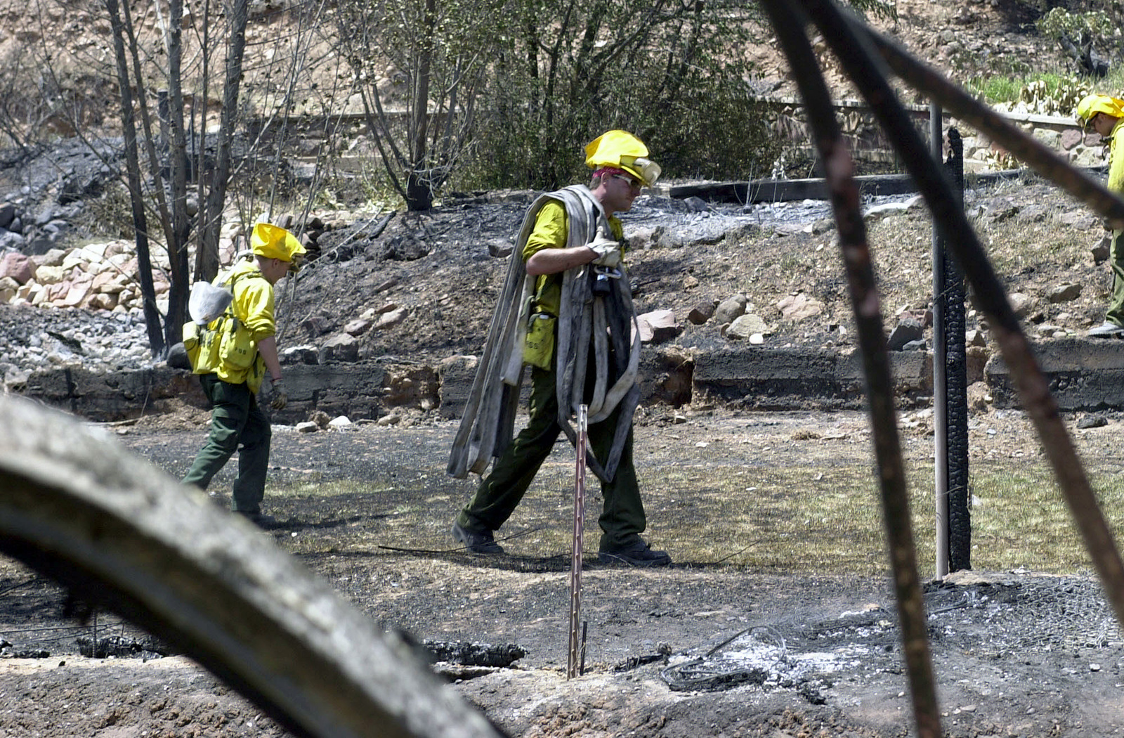 Firemen with a water hose and shovel walk along the charred landscape during the Coal Seam fires. The Coal Seam Fire started sometime in the mid-1970s as an underground fire burned along a rich vein of coal. Occassionally the fire breaks through to the surface. At this time it had burned 7,300 acres, damaged an estimated 40 structures, and caused the evacuation of 2,000 residents