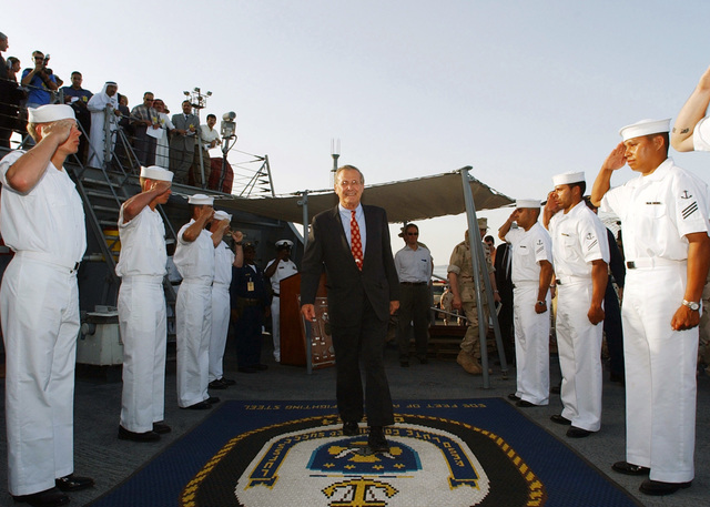 The Honorable Donald H. Rumsfeld (center), U.S. Secretary of Defense, arrives onboard the U.S. Navy Arleigh Burke Class (Flight I) Guided Missile Destroyer USS CARNEY (DDG 64) to meet its crewmembers on June 10, 2002, during his official tour of the Gulf Cooperation Council (GCC) member countries. The USS CARNEY is currently on station in the Persian Gulf in support of Operation Enduring Freedom. (DoD photo by PETTY Officer 2nd Class Michael Sandberg) (Released)