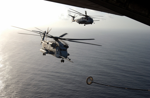 Two US Marine Corps (USMC) CH-53E Sea Stallion helicopters assigned to Marine Medium Helicopter Squadron 261 (HMM-261), conduct aerial refueling with a USMC KC-130 Hercules aircraft assigned to Marine Aerial Refueler Transport Squadron 252 (VMGR-252) during exercises conducted by the USMC 22nd Marine Expeditionary Unit (MEU) Special Operations Capable (SOC), over the Arabian Sea