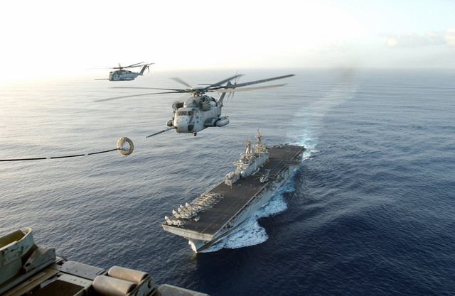 Two US Marine Corps (USMC) CH-53E Sea Stallion helicopters assigned to Marine Medium Helicopter Squadron 261 (HMM-261), conduct aerial refueling with a USMC KC-130 Hercules aircraft assigned to Marine Aerial Refueler Transport Squadron 252 (VMGR-252) during exercises conducted by the USMC 22nd Marine Expeditionary Unit (MEU) Special Operations Capable (SOC), in the Arabian Sea. The US Navy (USN) WASP CLASS; Amphibious Assault Ship, USS WASP (LHD-1), is underway in the background
