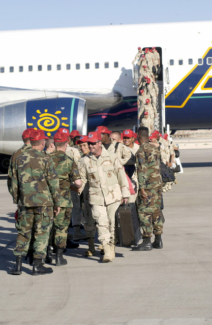 US Air Force (USAF) Airmen assigned to the 820th Red Horse Squadron (RHS), are greeted by Squadron personnel as the depart a Commercial Air Liner at Nellis Air Force Base (AFB), Nevada, at they return home following a six-month deployment in support of Operation ENDURING FREEDOM