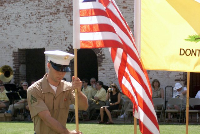 Corporal (CPL) Joseph F. Berrios, S-4, 24th Marine Expeditionary Unit (MEU), places an early version of the American Flag among other American Flags from the country's history, during Flag Day at Fort Macon, Morehead City, North Carolina