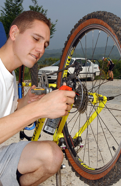 US Air Force (USAF) SENIOR AIRMAN (SRA) Patrick Dull applies a lubricant to his bike prior to competing in the US Forces Europe Mountain Bike Series held in the mountains near Aviano Air Base (AB), Italy